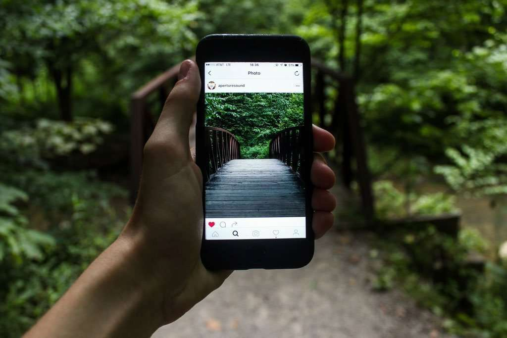 Do you know you can research your travel destination with Instagram? Here's how you search instagram for travel research using Hashtags. Picture of hand holding phone showing instagram of bridge and woods.