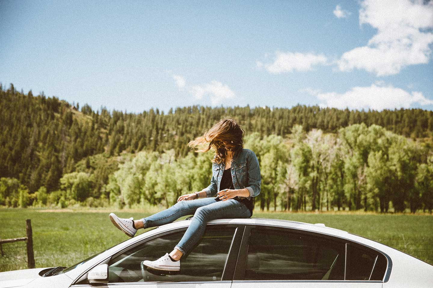 fly or drive girl sitting on car with wind blowing hair