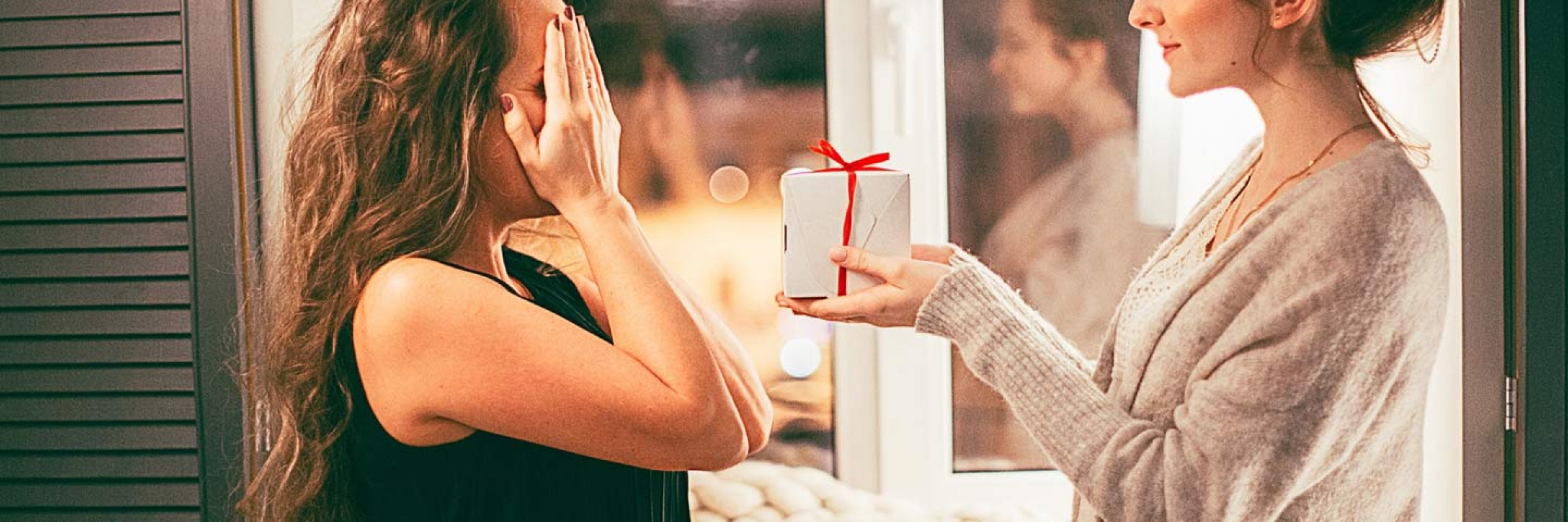 How to Give the Gift of Travel 2 women exchanging present wrapped in red bow