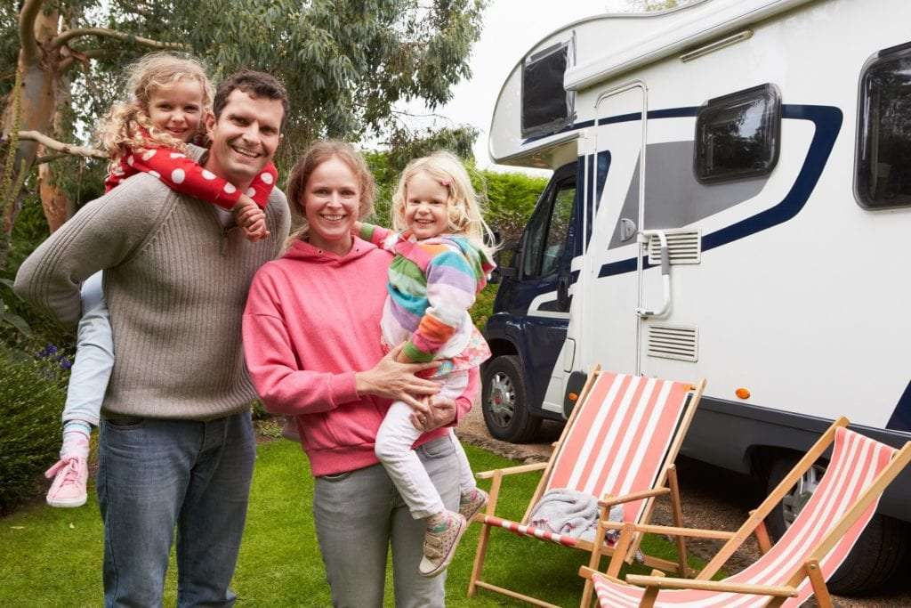 Family with two girls standing outside their Class C RV