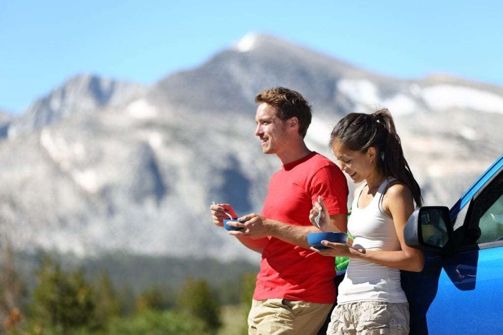 Couple on car road trip travel eating lunch break outdoors smiling happy. Multiracial couple, Asian woman, Caucasian man People in Yosemite National Park, California, United States.