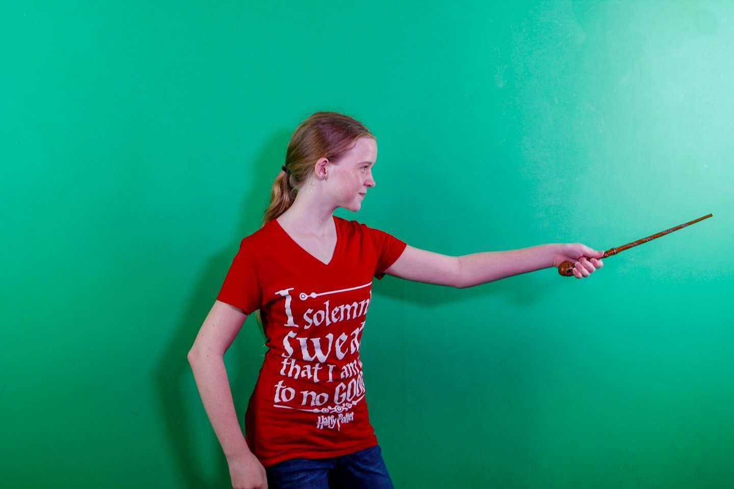 Girl with wand standing in front of a Green Screen.