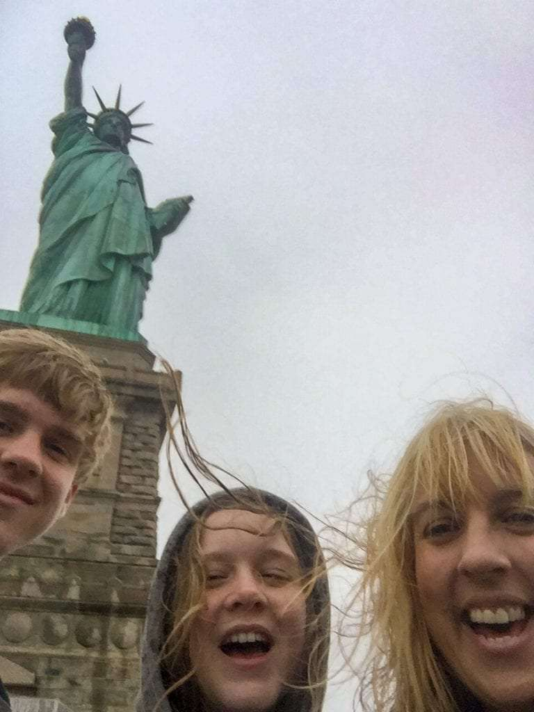 Visit the Statue of Liberty selfie with mom and 2 kids in front of the statue