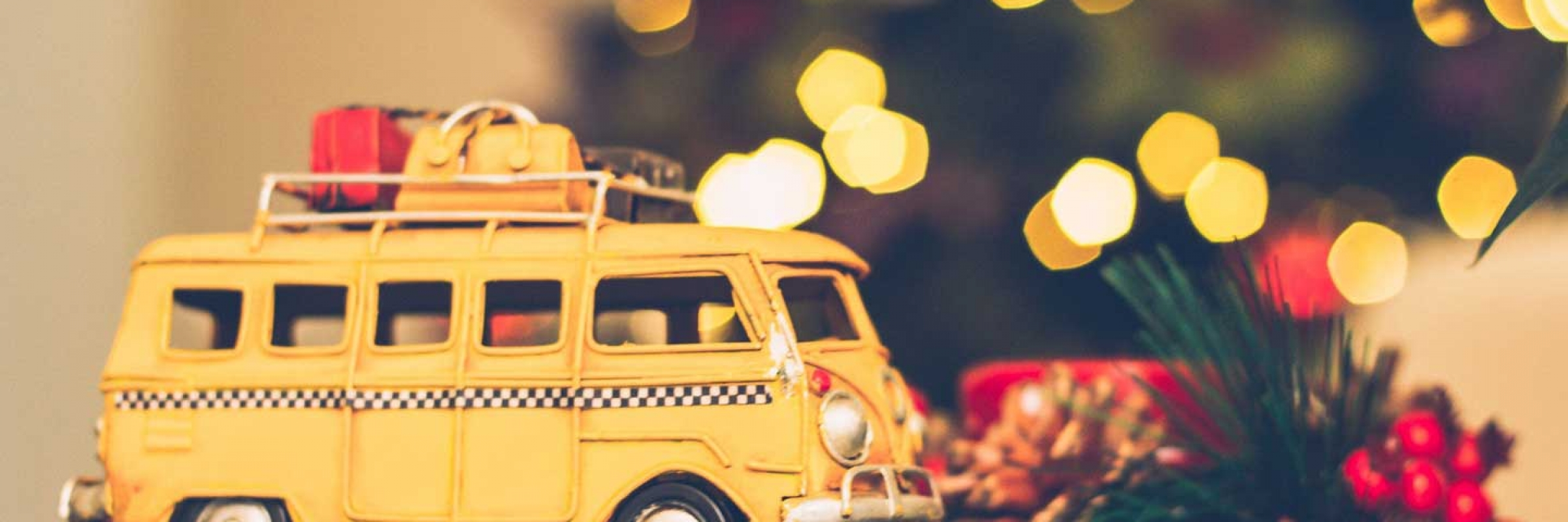 Holiday Gift Guide for Traveling Families with toy VW bus in front of Christmas Lights