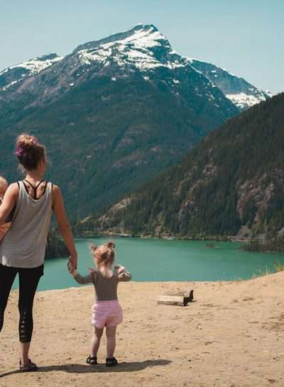 Family Travel Experiences Mother and baby in arms with young girl looking over lake with mountain.