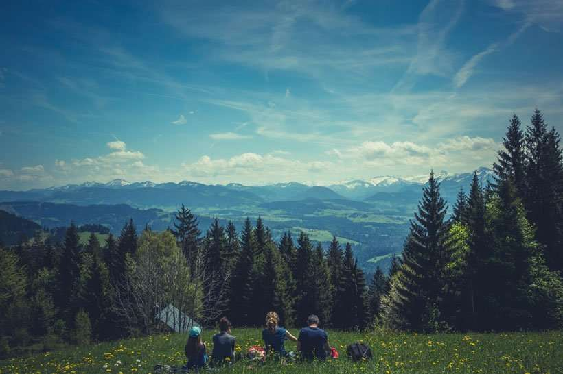 Family Travel Experiences family on grassy meadow overlooking pine trees and mountains with clear sky