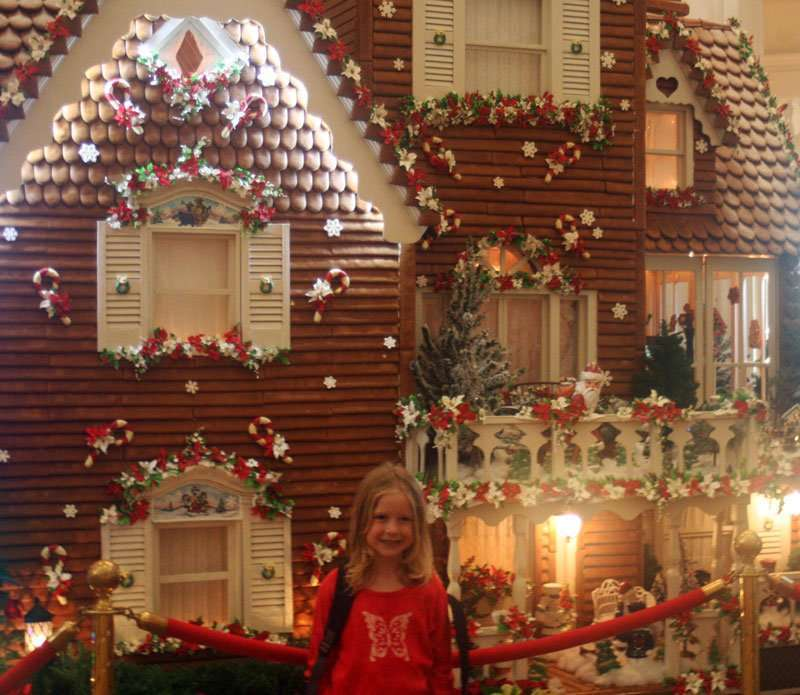 Christmas Celebrations in Florida Gingerbread house with girl in front