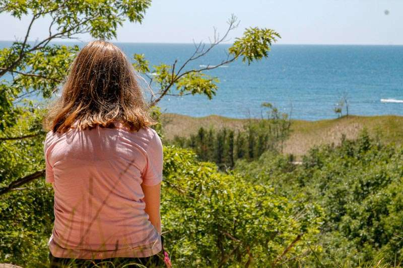 Girl on sand dune overlooking Lake Michigan, one of the best places to travel with kids