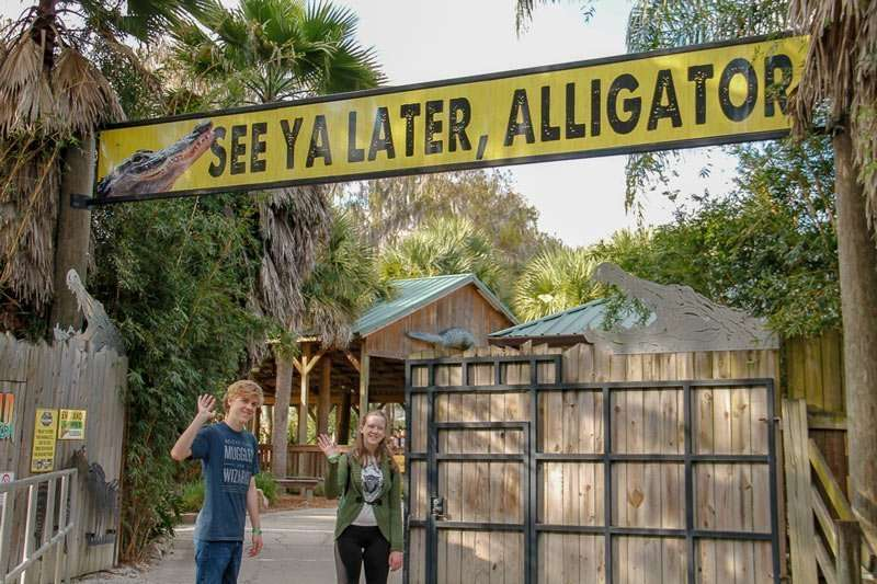 2 kids under a See Ya Later, Alligator sign