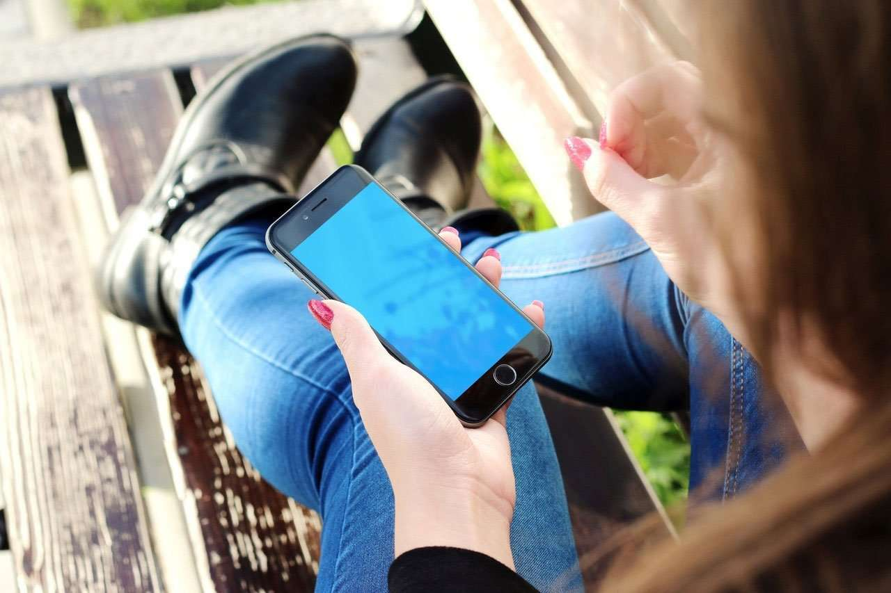 Women on bench holding phone for best travel apps