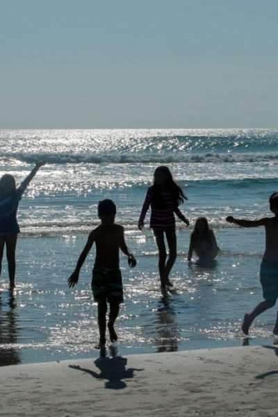 Get Everything You need for a Family Beach Vacation kids playing in ocean