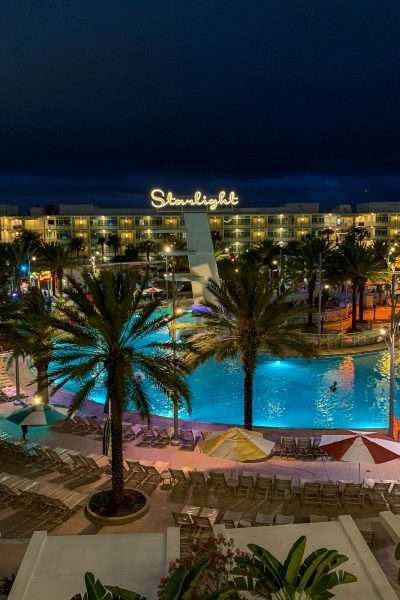 Night time view of Cabana Bay Beach Resort overlooking pool and hotel with palm trees