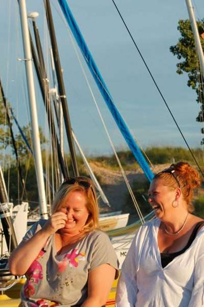 four women laughing in front of sailboats best multifamily vacation destinations