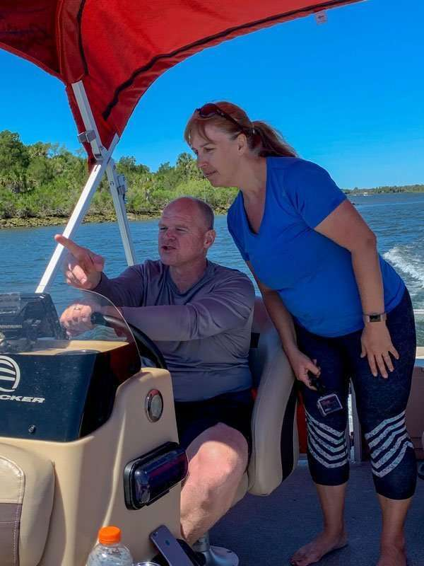 man and woman on pontoon boat in river on crystal river