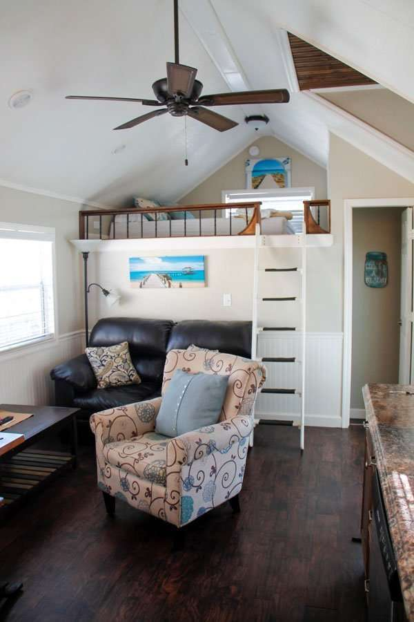 inside of cabin featuring loft and seating at Crystal Isles RV Resort