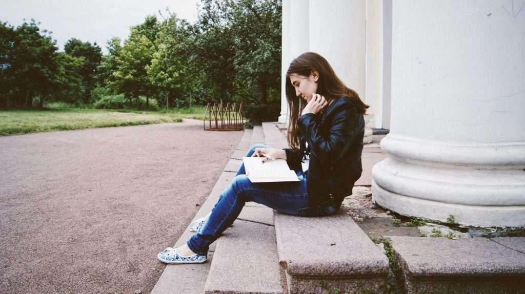 women reading on steps in park
