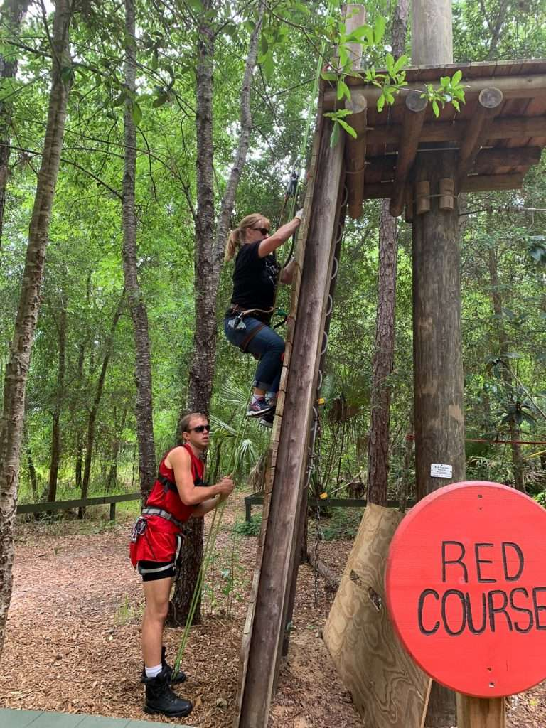 Climbing up the red course with guide at Orlando Tree Trek