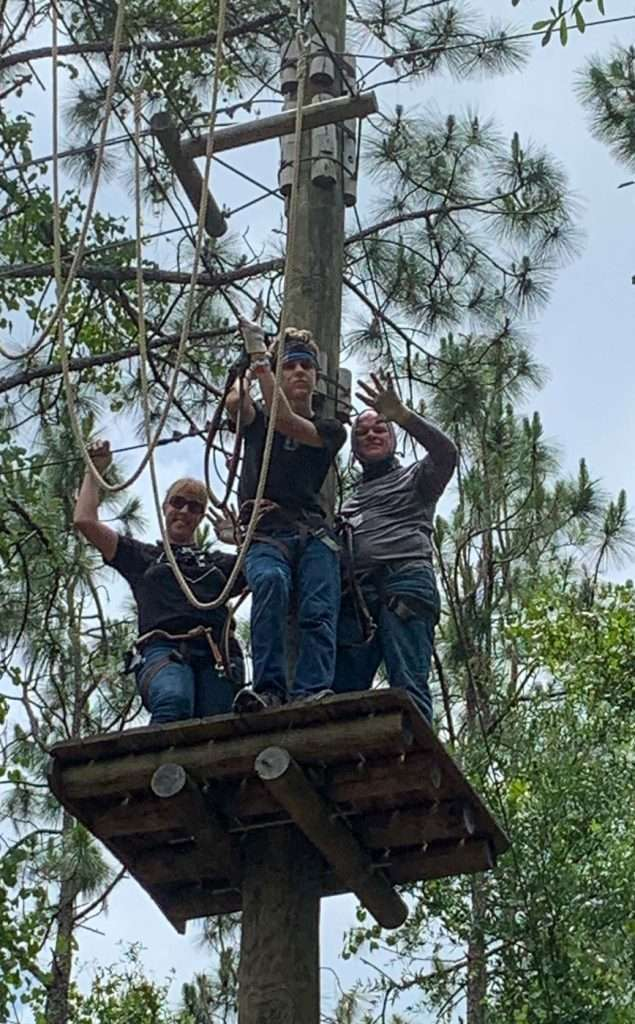 family on platform of a ropes course