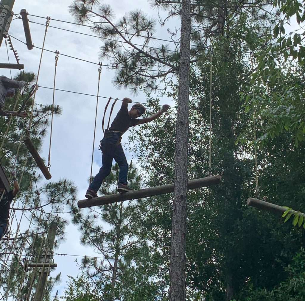 Boy climbing a ropes course