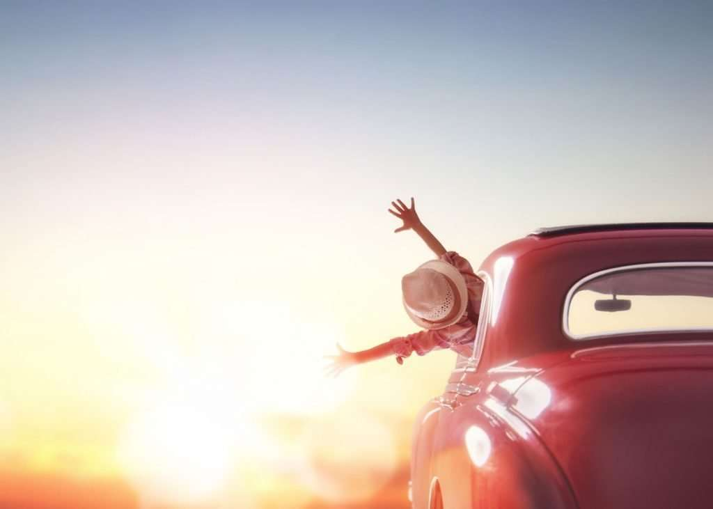 woman hanging out of car with sunset in the distance on an eco-friendly road trip
