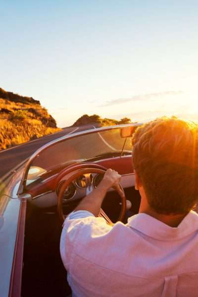couple driving into sunset in red convertible