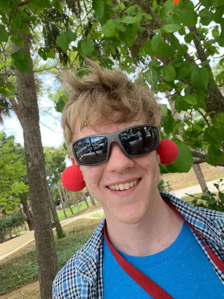 boy with sunglasses and red noses placed on ears