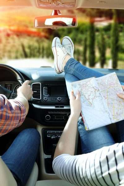Road trip with your partner, man and woman in car with map and feet on dashboard