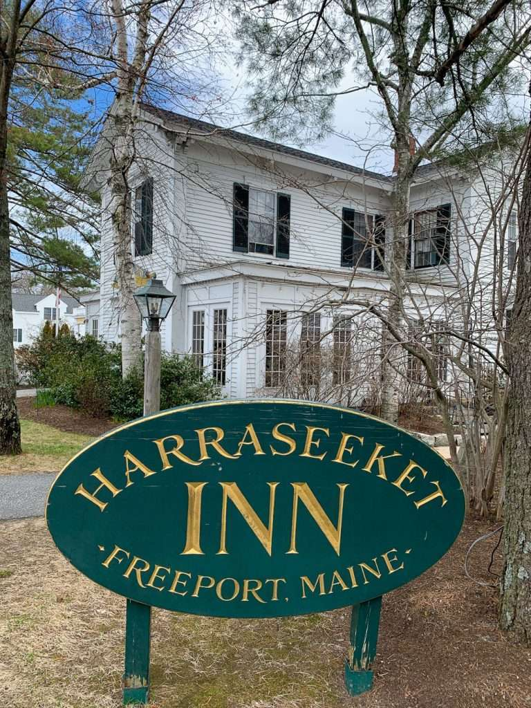 front of Harraseeket Inn with sign in Freeport Maine