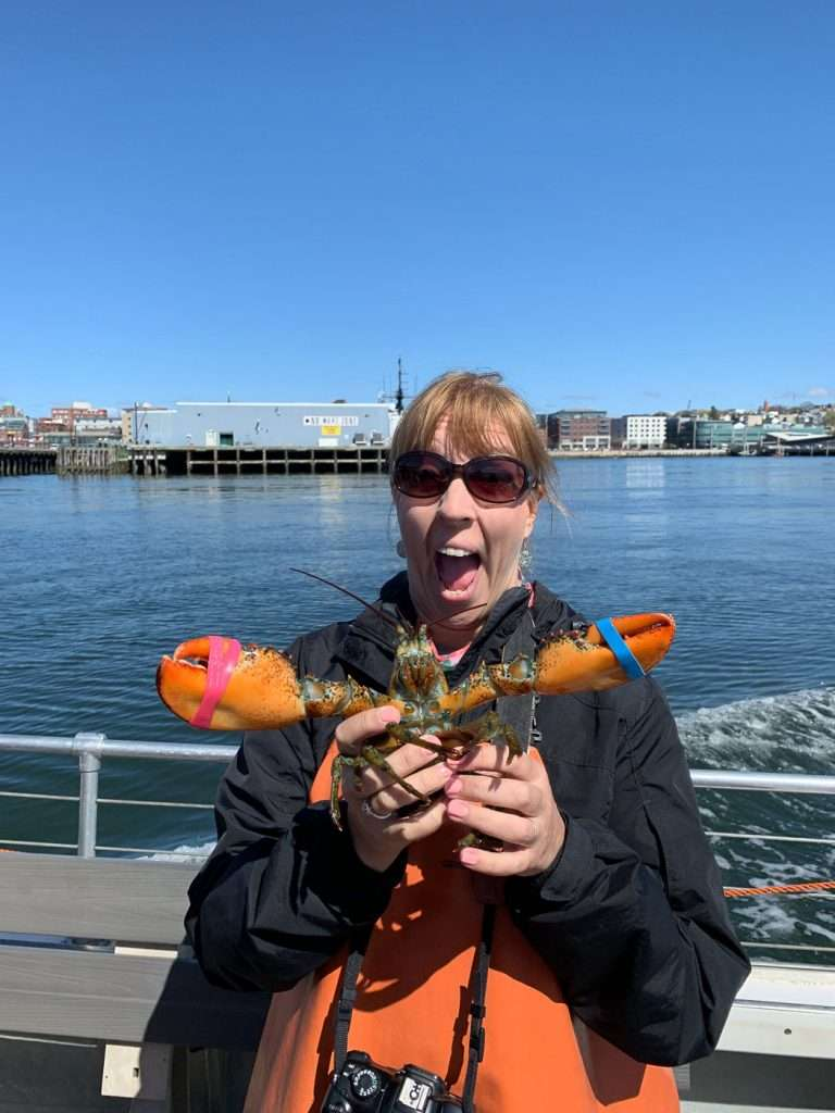 woman with lobster as one of the many things to do in Portland, Maine