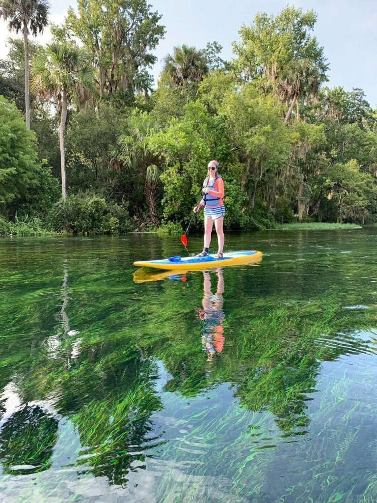 kayaking and paddleboarding along the Rainbow River is a top thing to do in Ocala. Shown is girl on paddleboard.