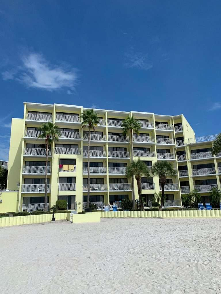 View of the Alden Suites Beachfront resort in St. Pete Beach from the beach. Yellow hotel building.