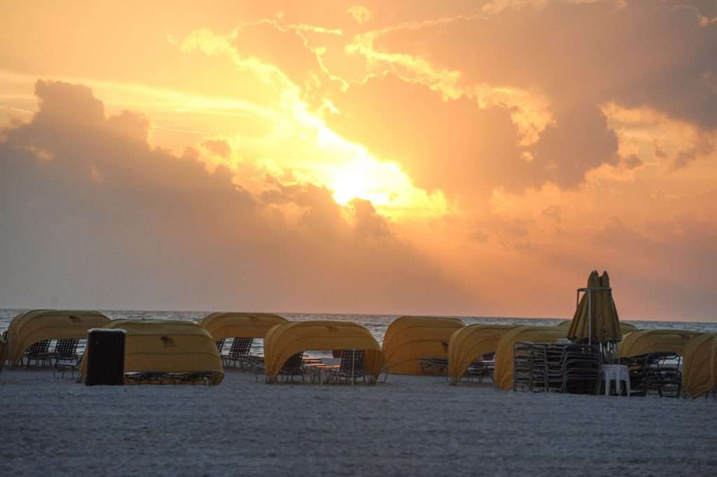 Bright orange sunset on St. Pete Beach with yellow Alden Suites cabanas