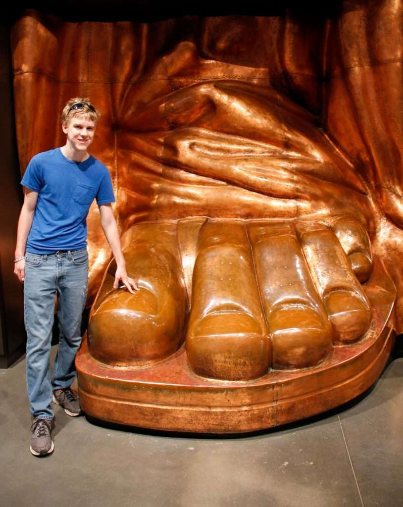 Boy with bronze Statue of Liberty foot.