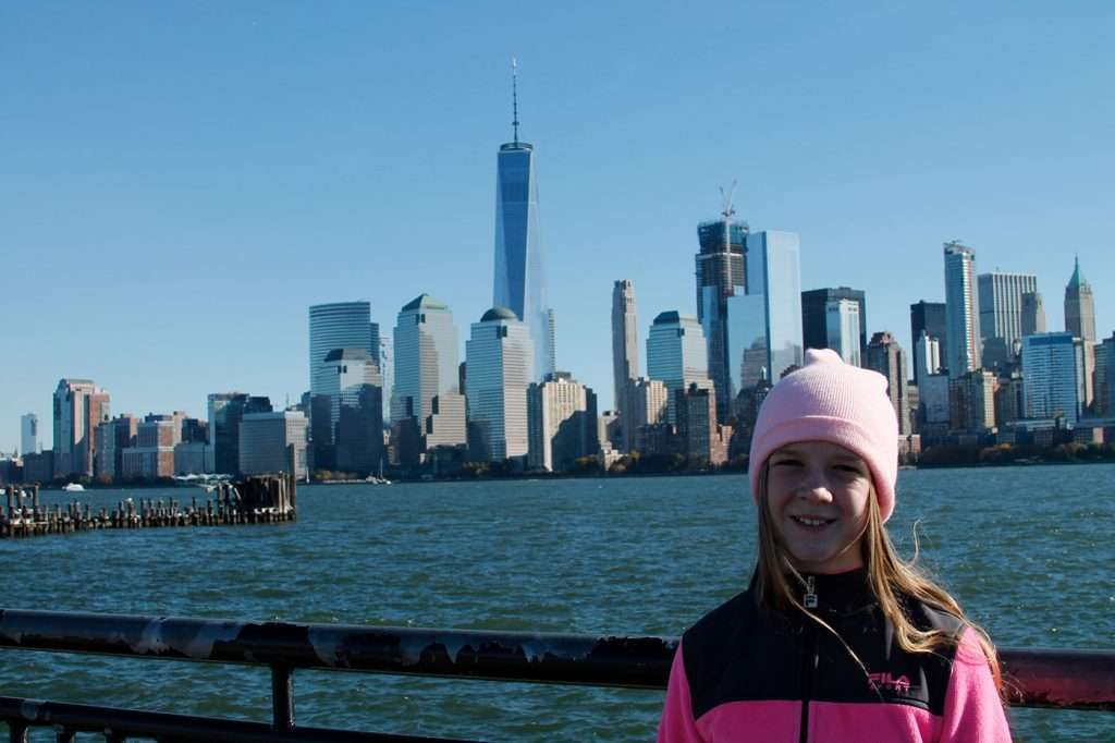 young girl standing in front of New York City Skyline.