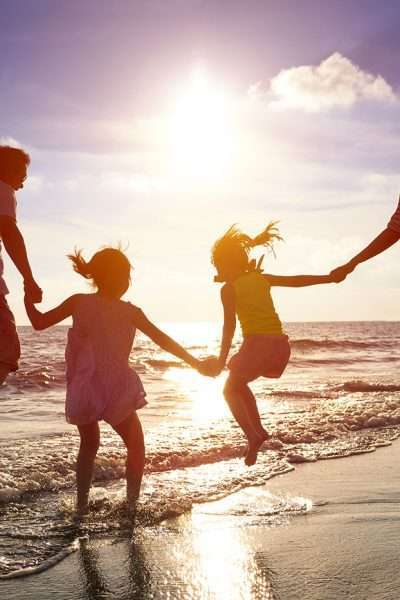 family jumping on beach for cheap destinations for family travel