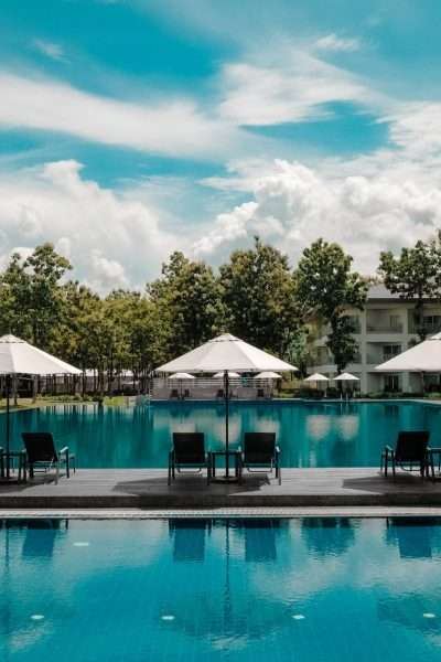 hotel pool with cabanas and tall trees in the background to demonstrate the best hotel rewards programs