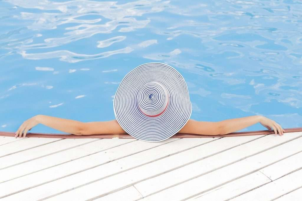 woman with hat lounging in pool enjoying her hotel rewards programs