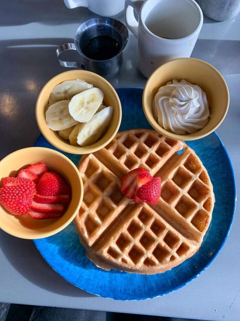 Breakfast including waffle, strawberrries, bananas, and coffee