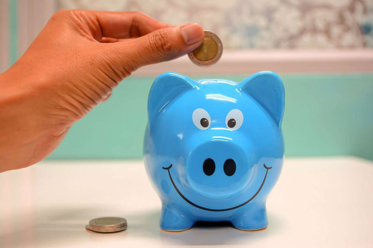 person putting coin in blue piggy bank to save money for travel