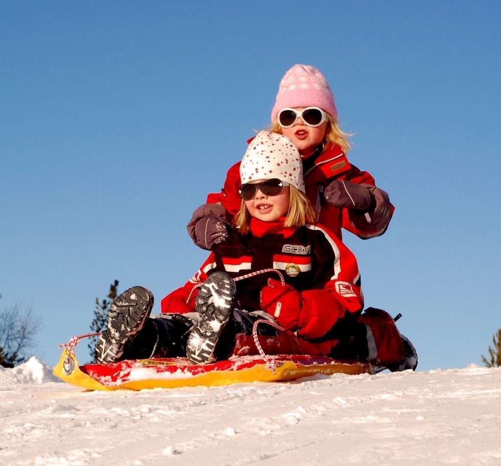 2 kids sledding in snow