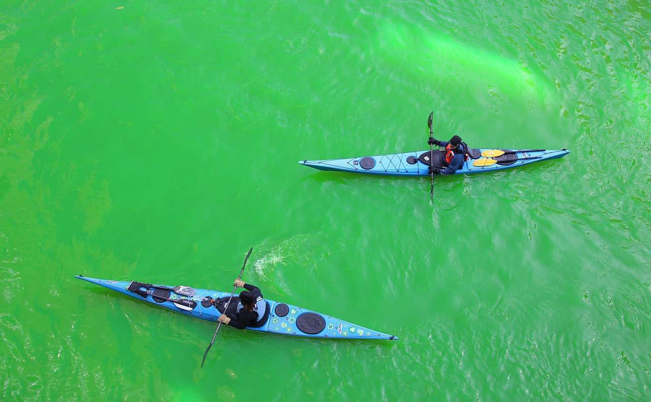 2 people kayaking in the green river in Chicago during St. Patricks Day