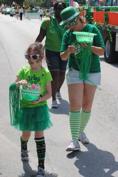 A St. Patricks Day Parade with woman and child handing out beads