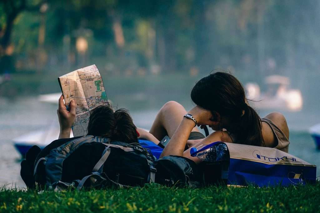 Couple laying on backpacks reading travel guide books