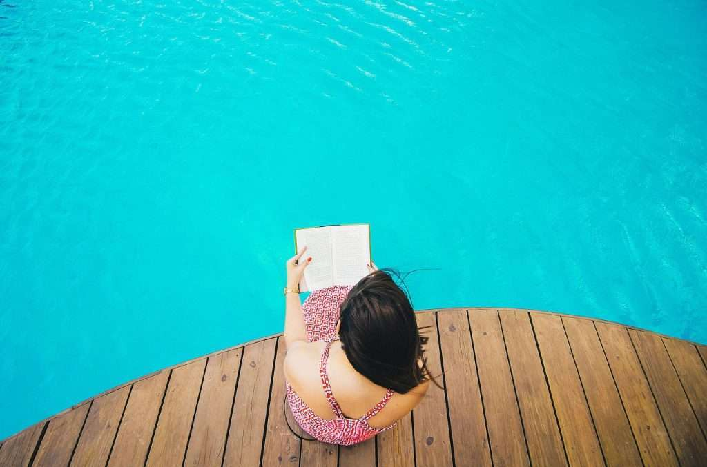 women by pool reading travel memoirs