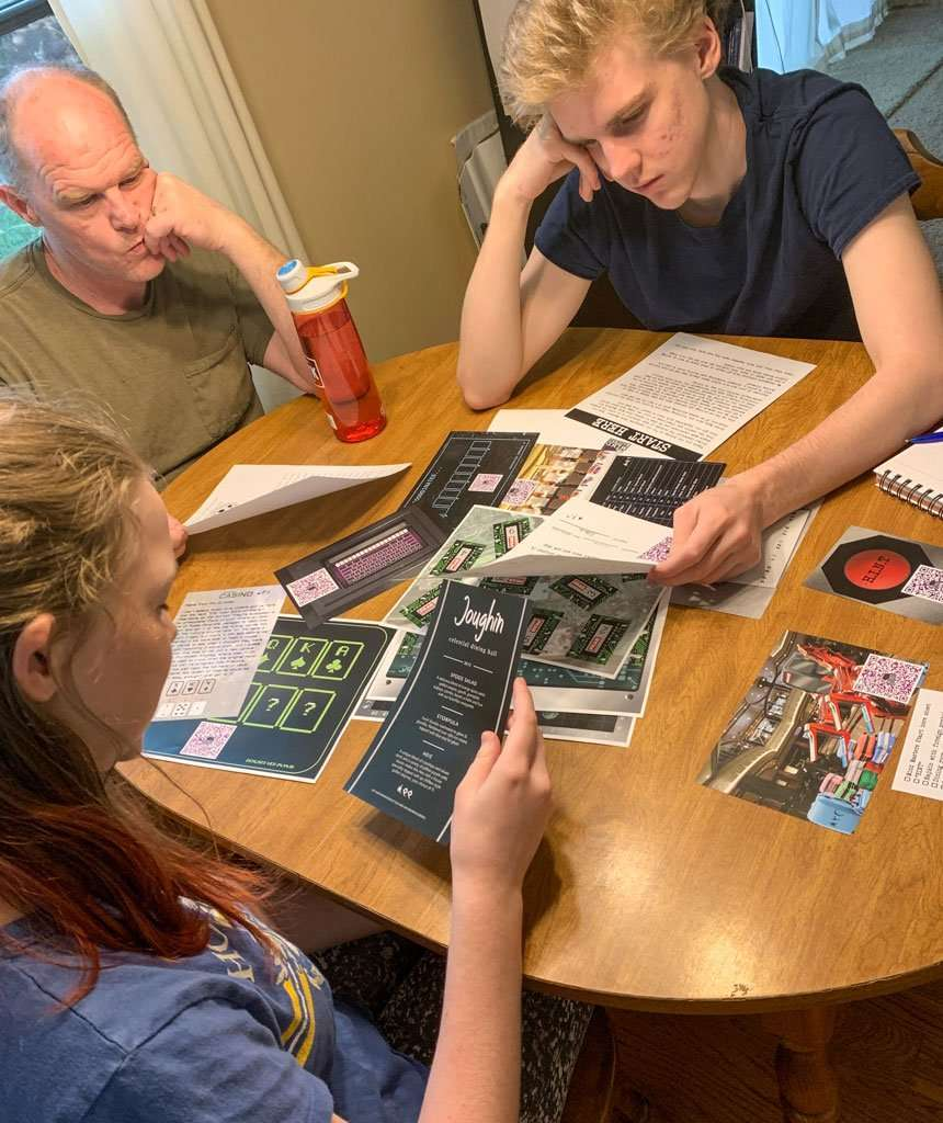 family gathered around table playing escape room game
