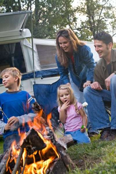 family in front of camping trailer and campfire for rv travel