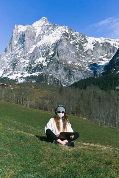 women wearing travel themed face masks by mountain.