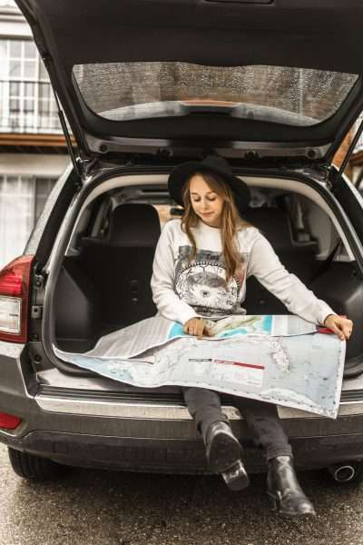 girl in the back of a car looking at a map planning family road trips