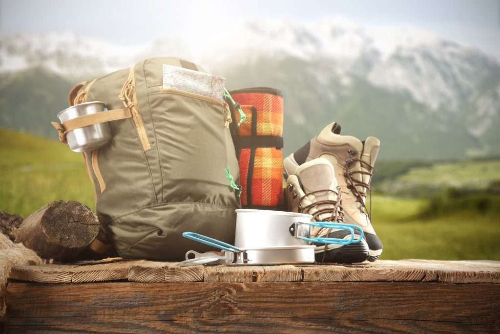 Camping gear on a table in front of a mountain as a camping checklist