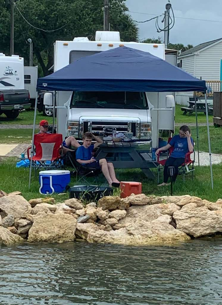 family camping in a rented RV in front of river